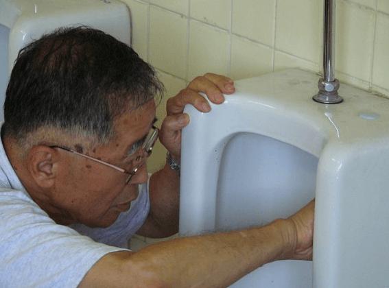 トイレ掃除をするイエローハットの創業者の鍵山秀三郎氏の写真