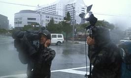 台風の最中の中継カメラマンたち